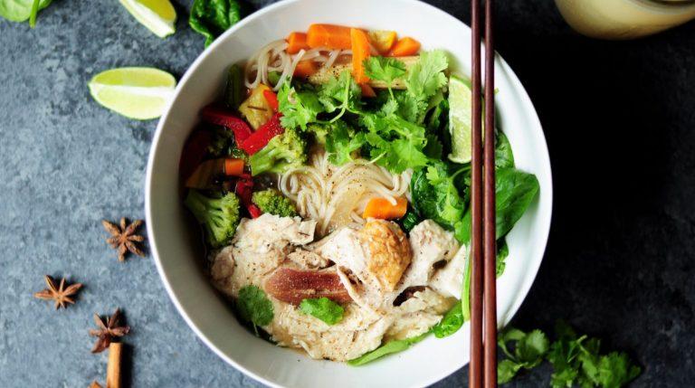 Asiatisk måltid med nudler og grøntsager serveret i hvid skål med spisepinde